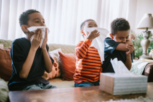 Three brothers sit on the couch blowing their noses