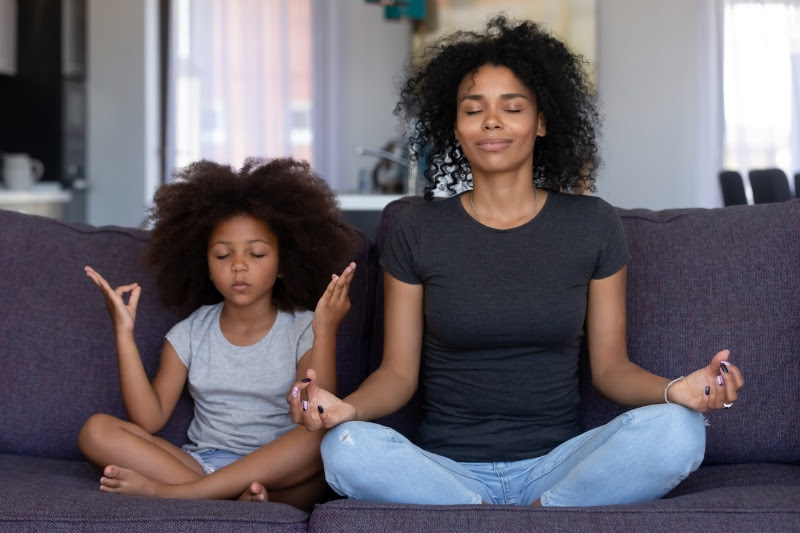 Black mom and daughter meditate together on the couch
