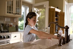 Girl washing her hands to stay healthy during flu season
