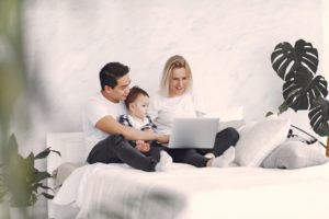 Family using the computer together on their bed
