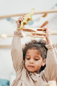girl playing with wooden dinosaurs
