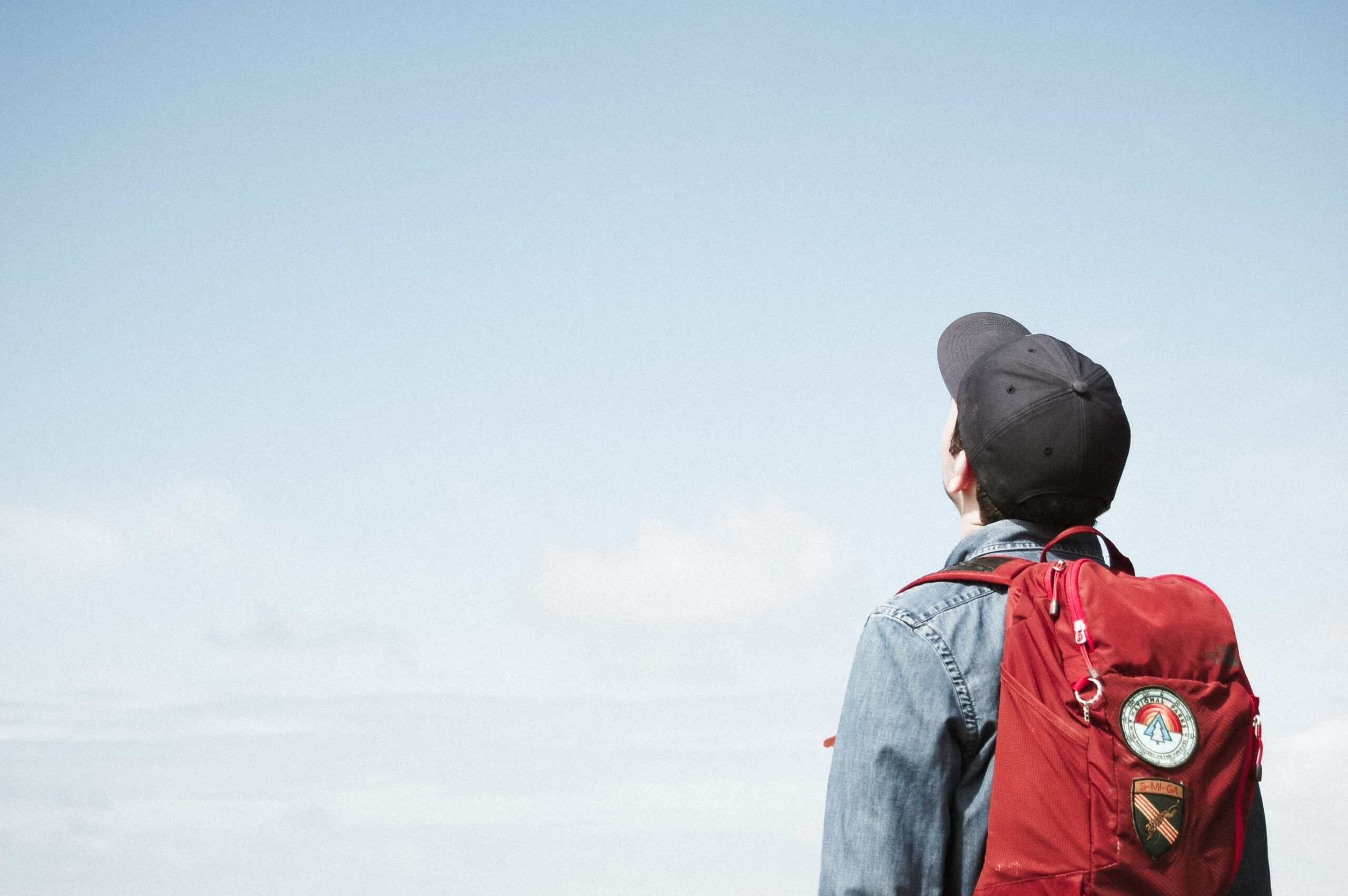 Boy with a backpack looking up at the sky